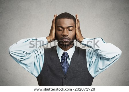 Closeup portrait peaceful, tranquil, relaxed looking, young corporate business man covering his ears, eyes closed, isolated black background. Hear no evil concept. Human emotions, facial expressions - stock photo