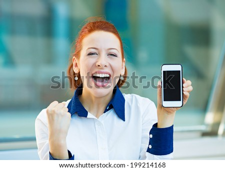 Closeup portrait, photo attractive happy smiling young business woman presenting holding smartphone, screen, celebrating successes, pumping fists isolated background corporate office. Positive emotion - stock photo