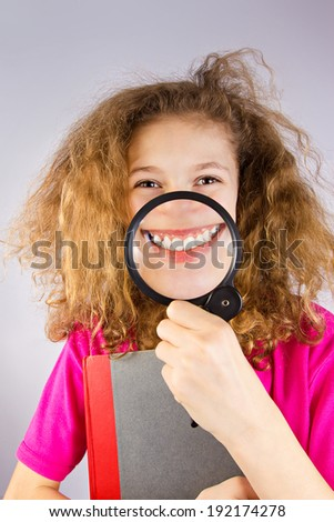Closeup portrait, picture, headshot happy, joyful little teenage, funny, smiling girl with magnifying glass showing white teeth isolated grey background. Positive emotions, facial expression, attitude - stock photo