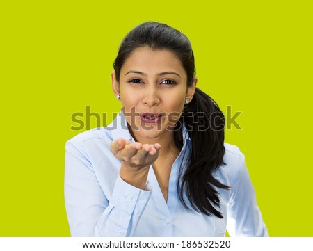 Closeup portrait, pretty young woman puckering up lips to blow kiss at you camera gesture, isolated green background. Positive human emotion facial expression feeling, sign symbol body language - stock photo