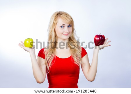 Closeup portrait puzzled, thinking, thoughtful young woman, girl, holding red, green apples, uncertain which one to chose. Human face expressions, emotion, reaction, attitude, life perception, variety
