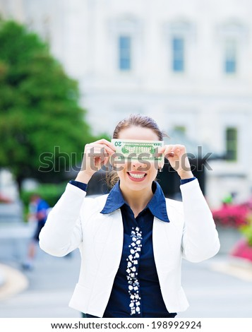 Closeup portrait quiet corrupt politician in washington dc, woman holding covering her eyes with dollar bills isolated Capitol building background. Human nature, life perception Greed politics concept - stock photo