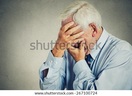 Closeup portrait sad depressed, stressed, thoughtful, senior, old man, gloomy, worried, covering his face isolated gray wall background. Human face expressions, emotion, feelings, reaction, attitude - stock photo