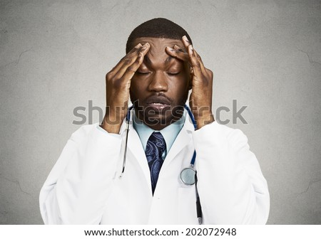 Closeup portrait sad health care professional with headache, stressed, holding head with hands. Nurse, doctor with migraine overworked, overstressed isolated black background. Negative human emotions - stock photo