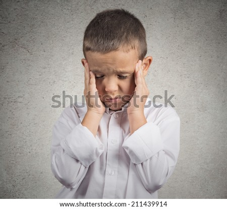 Closeup portrait sad, worried Stressed teenage, young boy, having headache, hands on head, isolated grey wall background. Negative human emotions, feelings, life perception, body language.  - stock photo