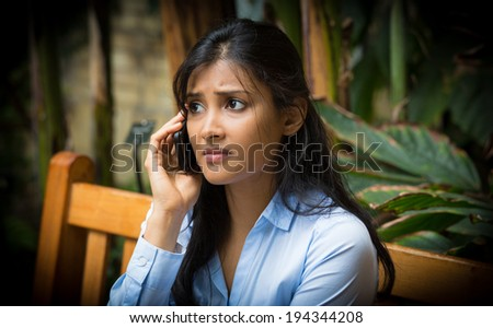 Closeup portrait, sad, worried young woman talking on phone, sitting on bench, isolated trees background, dark vignetting. Negative human emotions, facial expressions, feelings, reaction. Bad news. - stock photo