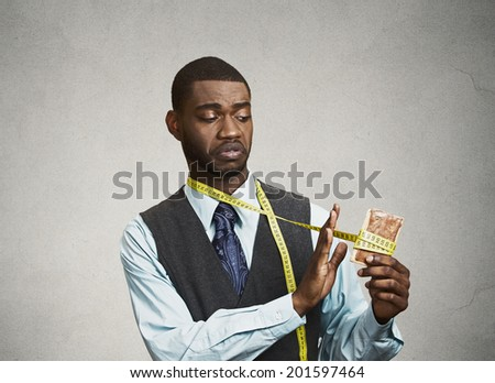 Closeup portrait sad, young, confused man holding, looking at fatty, sweet cookie with measuring tape around, trying to withstand resist temptation to eat it isolated black background. Face expression - stock photo