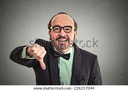 Closeup portrait sarcastic middle aged man showing thumbs down sign hand gesture happy someone made mistake lost failed isolated grey wall background. Negative emotion face expression feeling attitude - stock photo