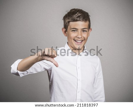 Closeup portrait sarcastic young man showing thumb down sign, hand gesture, happy that someone made mistake, lost, failed isolated grey wall background. Human emotions, facial expressions, feelings