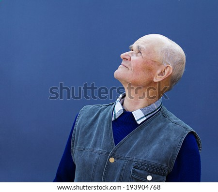 Closeup portrait senior, elderly, mature man, grandfather looking up with hope, thinking, daydreaming, isolated blue background. Human facial expressions, emotions, feelings, reaction life perception - stock photo
