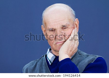 Closeup portrait senior, elderly, mature, old sad depressed man, deep in thought, thinking, realizing truth, looking down isolated blue background. Human face expressions, emotions, feeling, reaction - stock photo