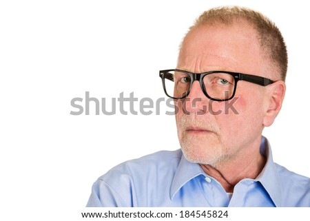 Closeup portrait, senior mature business man in black glasses, suspicious annoyed looking being cautious, careful, thinking, of his own mind, isolated white background. Emotion, facial expression - stock photo