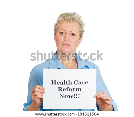 Closeup portrait senior mature business woman, elderly lady, employee holding health care reform now! sign, isolated white background. Government, federal politics, congress, insurance policy debate