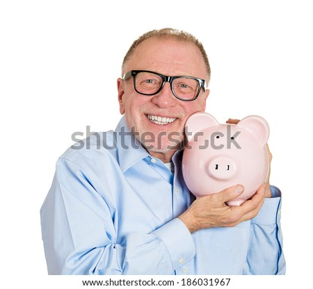 Closeup portrait, senior mature, happy, successful, enthusiastic affectionate sensitive nerd man in black glasses hugging piggy bank, isolated white background. Financial decisions, money saving, fund