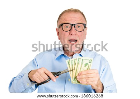 Closeup portrait, senior mature man, business worker employee, corporate agent representative cutting budget, trimming dollar bills, cash, money with scissors, isolated white background. Emotions - stock photo