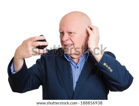 Closeup portrait, senior mature man feeling head, surprised by what he sees on skin or seeing bad news on cellphone, isolated white background. Negative human facial expressions, emotion feeling - stock photo