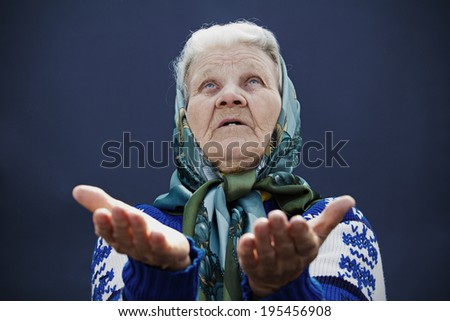 Closeup portrait, senior mature, old woman praying, eyes opened, looking up, hoping for best, asking forgiveness, miracle isolated blue background. Positive human emotions, facial expression feelings - stock photo