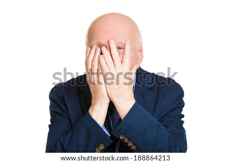 Closeup portrait, senior mature, scared, terrified, horrified, man peeking through covered hand, cant believe what he sees, isolated white background. Negative emotion facial expression feelings.