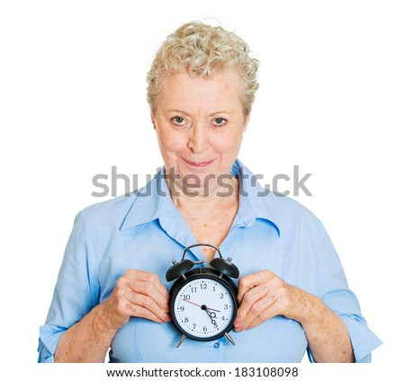 Closeup portrait, senior mature smiling business woman, successful happy old executive, banker, employee holding alarm clock, isolated white background. Human positive face expressions, emotions - stock photo