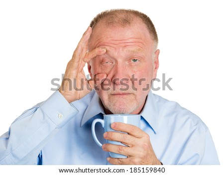 Closeup portrait senior mature, tired, falling asleep business man holding cup, struggling not to crash, stay awake, keep eyes opened, isolated white background. Human emotion, facial expression - stock photo