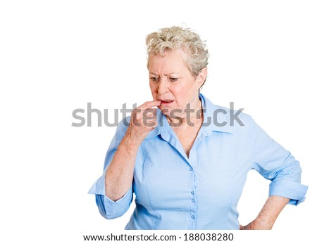 Closeup portrait, senior mature woman, finger in mouth, trying to remember something, isolated white background. Positive human emotion facial expression feelings, attitude, reaction situation - stock photo