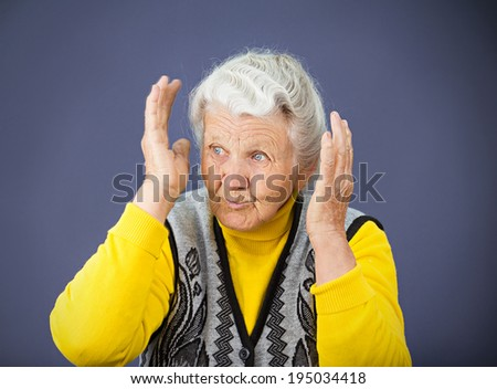 Closeup portrait, senior mature woman looking sideways, hearing voices, surprised in disbelief, hands on head, isolated blue background. Negative human emotions, facial expressions, feelings, reaction - stock photo