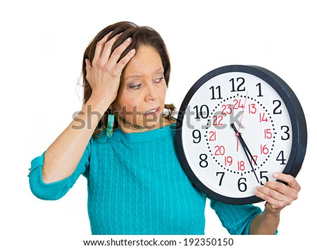 Closeup portrait senior woman worker, holding clock looking anxiously, pressured by lack, running out of time, isolated white background. Human face expression, emotion, reaction, corporate life style - stock photo