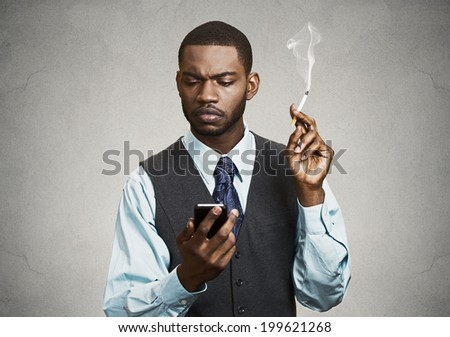 Closeup portrait serious, stressed worried business man, executive reading bad news on smart phone holding mobile, smoking cigarette isolated black grey background. Human face expressions, emotions - stock photo