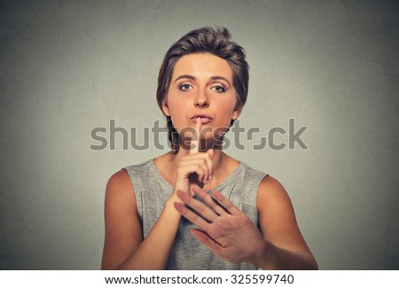 Closeup portrait serious upset woman finger, hand on lips, shhh gesture asking be quiet silence isolated on gray wall background. Negative facial expression sign emotion feelings, body language - stock photo