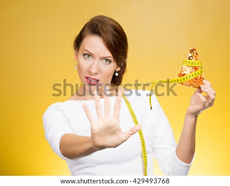 Closeup portrait serious woman saying no to fatty pizza with measuring tape around, trying to withstand, resist temptation to eat it isolated on yellow background. Human facial expression