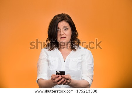 Closeup portrait, shocked, business woman, corporate employee looking at cell phone, seeing bad text message, email, news isolated orange background. Negative human emotion facial expression reaction - stock photo