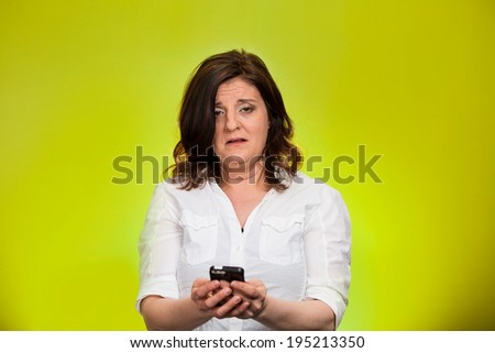 Closeup portrait, shocked, business woman, corporate employee looking at cell phone, seeing bad text message, email, news isolated green background. Negative human emotion facial expression reaction - stock photo