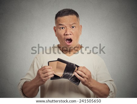 Closeup portrait shocked puzzled unhappy business man worker employee, funny looking guy, student, holding empty wallet isolated grey wall background. Bankruptcy financial difficulty. Face expressions - stock photo
