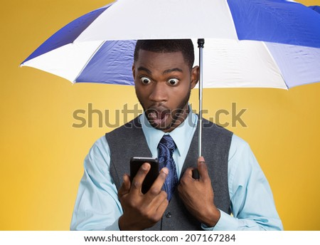 Closeup portrait shocked surprised business man corporate executive reading bad, breaking news on smart phone holding umbrella protected from rain isolated yellow background. Face expression, emotion  - stock photo