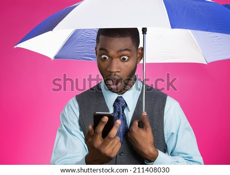 Closeup portrait shocked, surprised business man, corporate executive reading bad, breaking news on smart phone holding umbrella protected from rain isolated pink background. Face expression, emotion  - stock photo