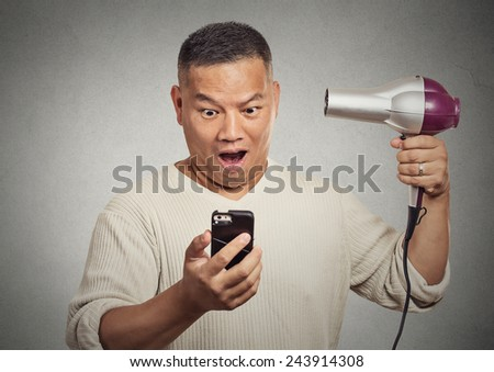 Closeup portrait shocked surprised man looking on smartphone holding hairdryer something blows his mind isolated grey background. Face expression emotion. Stressful life breaking mind blowing news - stock photo