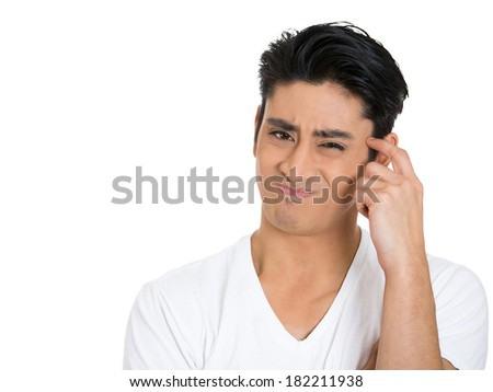 Closeup portrait skeptical young man, funny, suspicious annoyed looking man, being cautious, careful, alert, attentive, thinking, on his own mind isolated white background. Emotion, facial expression - stock photo