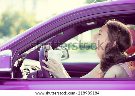 Closeup portrait sleepy, tired, fatigued, exhausted young attractive woman driving her car after long hour trip, isolated street traffic background. Transportation, sleep deprivation, accident concept - stock photo