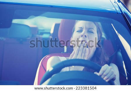 Closeup portrait sleepy tired fatigued exhausted young attractive woman driving her car in street traffic after long hour trip windshield front view. Transportation sleep deprivation accident concept - stock photo