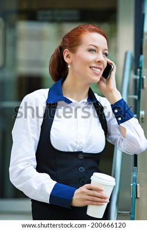 Closeup portrait, smiling attractive successful businesswoman, entrepreneur, corporate employee talking on smart, cellphone outdoors, on coffee break, isolated background company office building