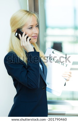 Closeup portrait, smiling attractive, successful businesswoman, entrepreneur, corporate employee talking on cellphone while walking in company building hallway, isolated background office windows - stock photo