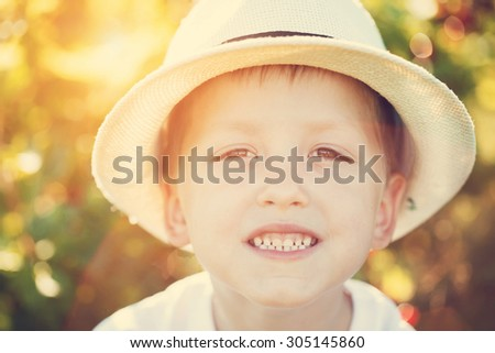 Closeup portrait smiling boy in a hat. Summertime. Toning image - stock photo