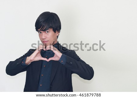 Closeup portrait smiling cheerful happy Asian business man in black suit making heart sign with hands.