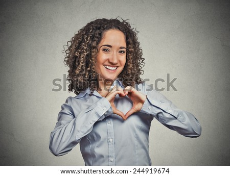 Closeup portrait smiling cheerful happy young woman making heart sign with hands isolated grey wall background. Positive human emotion expression feeling life perception attitude body language - stock photo