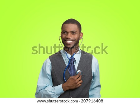 Closeup portrait smiling executive man, business person, worker listening to his heart with stethoscope isolated green background. Preventive medicine, financial condition concept. Face expressions - stock photo