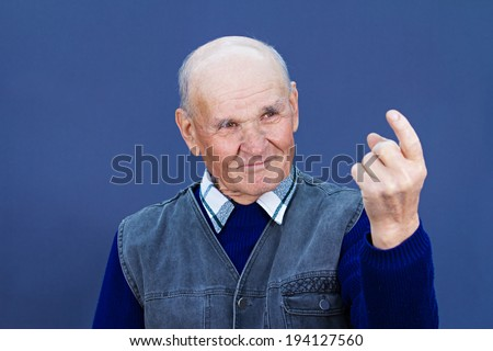 Closeup portrait, smiling, happy, elderly, senior, old man, grandfather giving come here sign with hand, finger, asking someone to approach him, help, isolated blue background. Human expression - stock photo