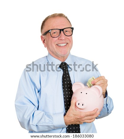 Closeup portrait, smiling nerd, senior mature woman depositing money into piggy bank, isolated white background. Smart currency financial investment wealth decisions. Budget management and savings