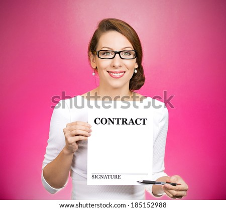 Closeup portrait smiling, young business woman with glasses, holding contract pointing with pen at space for signature isolated pink background. Positive face expression, emotion, attitude, perception