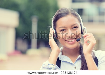 Closeup portrait smiling young female customer service representative call center agent support staff operator with phone headset isolated background with trees city building. Positive face expression - stock photo