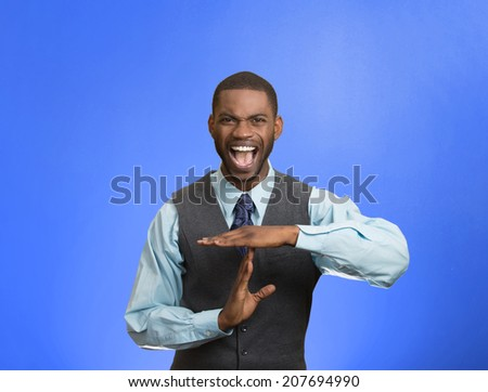Closeup portrait stressed angry young business man showing time out gesture with hands, isolated blue background. Negative human emotions, facial expressions, sign, symbols, body language, attitude - stock photo